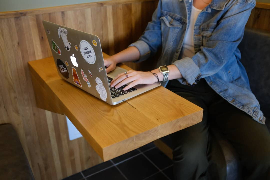 A person using a laptop computer sitting on top of a wooden table