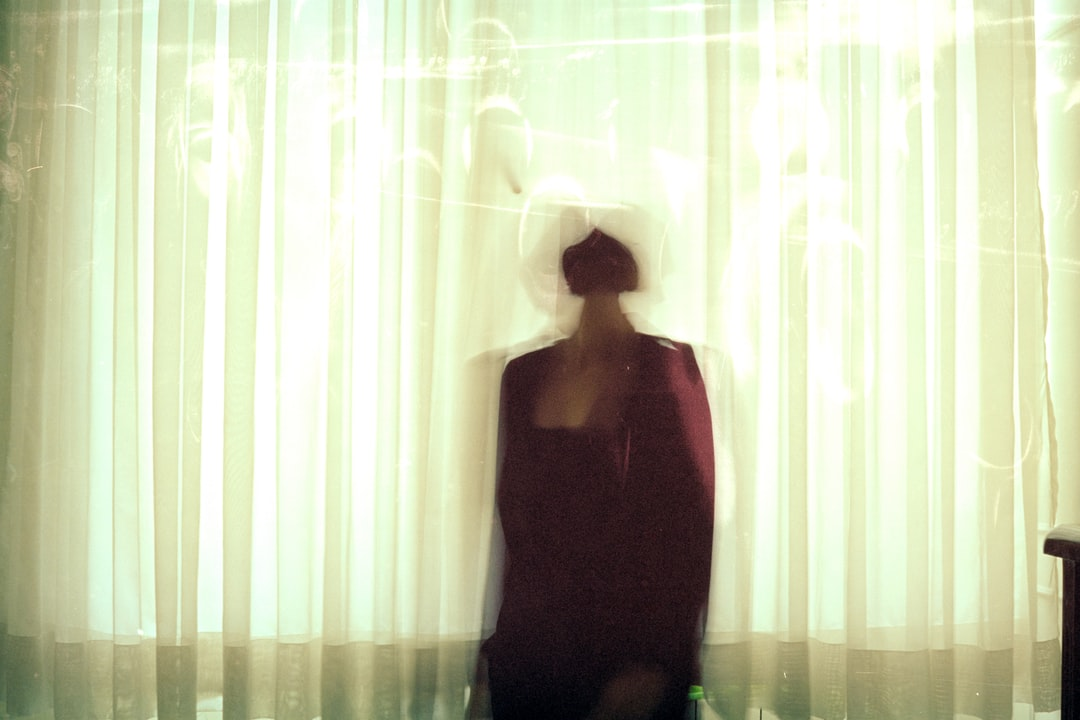 A person sitting in front of a curtain